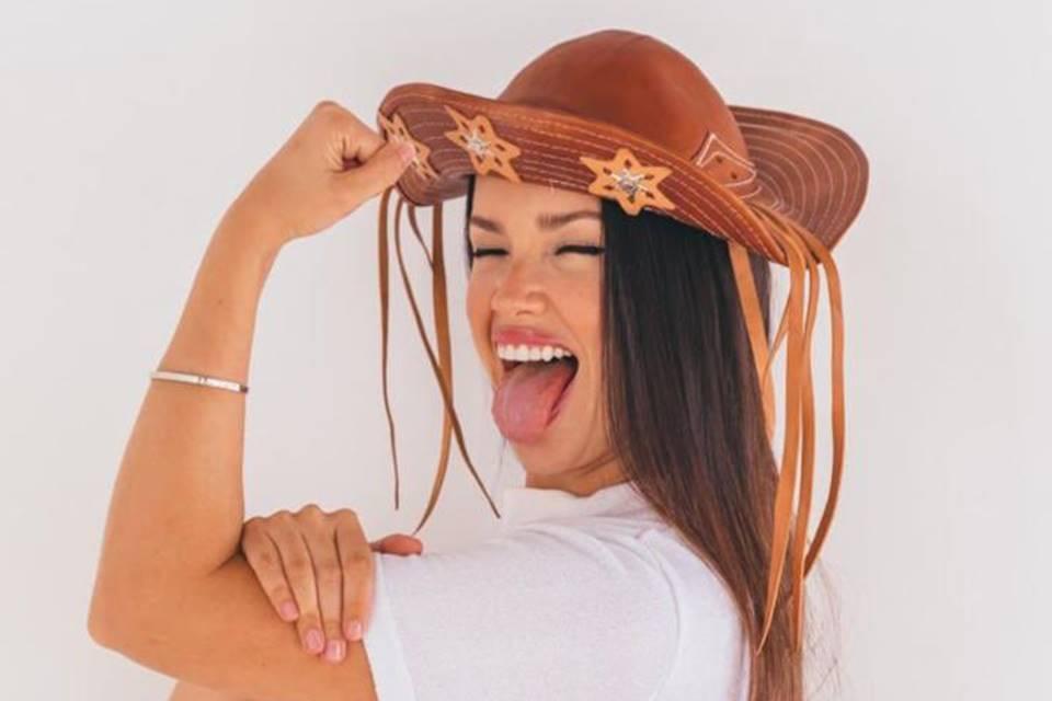 """Juliette está usando um chapéu típico de cangaceiros, do Nordeste. Ela está com os olhos fechados e a língua de fora. Ela usa uma camisa branca lisa. A imagem estampa a matéria: """"Final BBB 21: relembre a trajetória de Juliette no reality"""""""