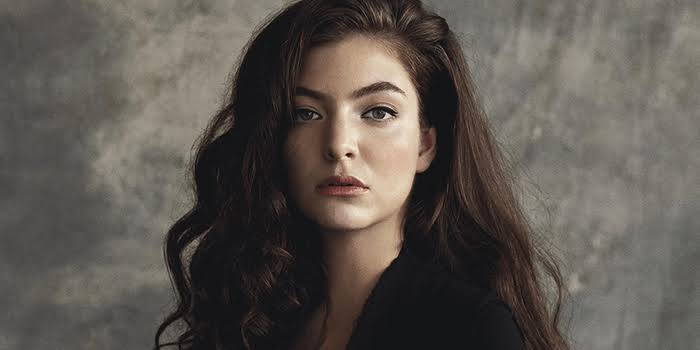 Lorde faz cover de rock igual Miley Cyrus. Na foto, Lorde usa uma blusa preta e o cabelo preto com uma parede atrás cinza