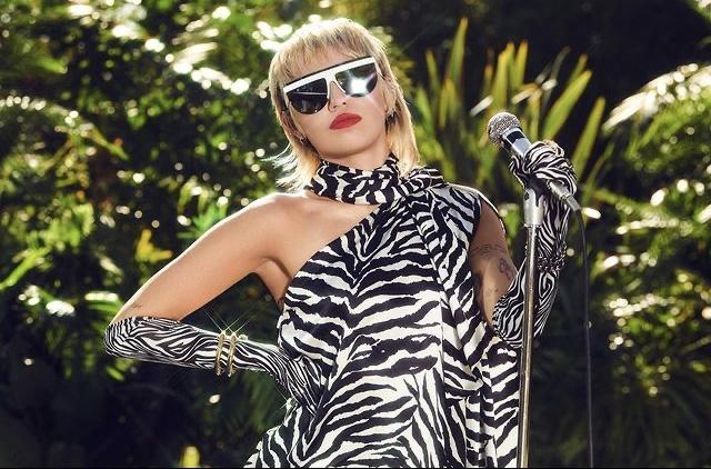 Miley Cyrus faz cover de rock no NCAA. Na foto, ela aparece vestindo um vestido estampado de zebra, com luvas estampado de zebra e um óculos escuro. As mãos no microfone.
