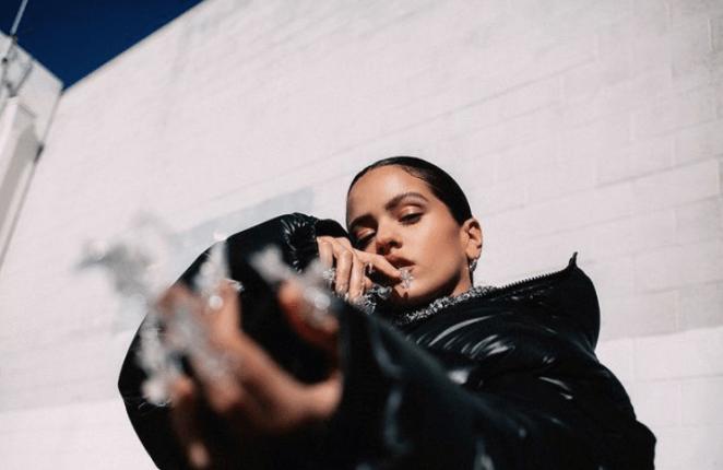 Novo álbum de Rosalía em 2022. A cantora parece usando um casaco preto de couro e unhas com pedras erguidas pra frente da câmera.
