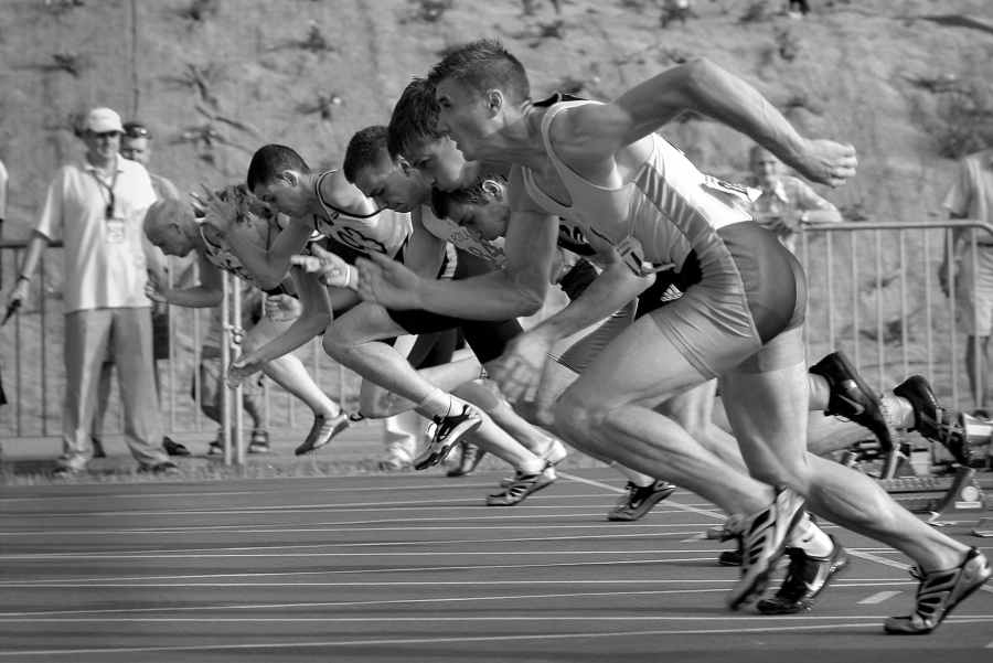 athletes running on track and field oval in grayscale photography  prepare for a race