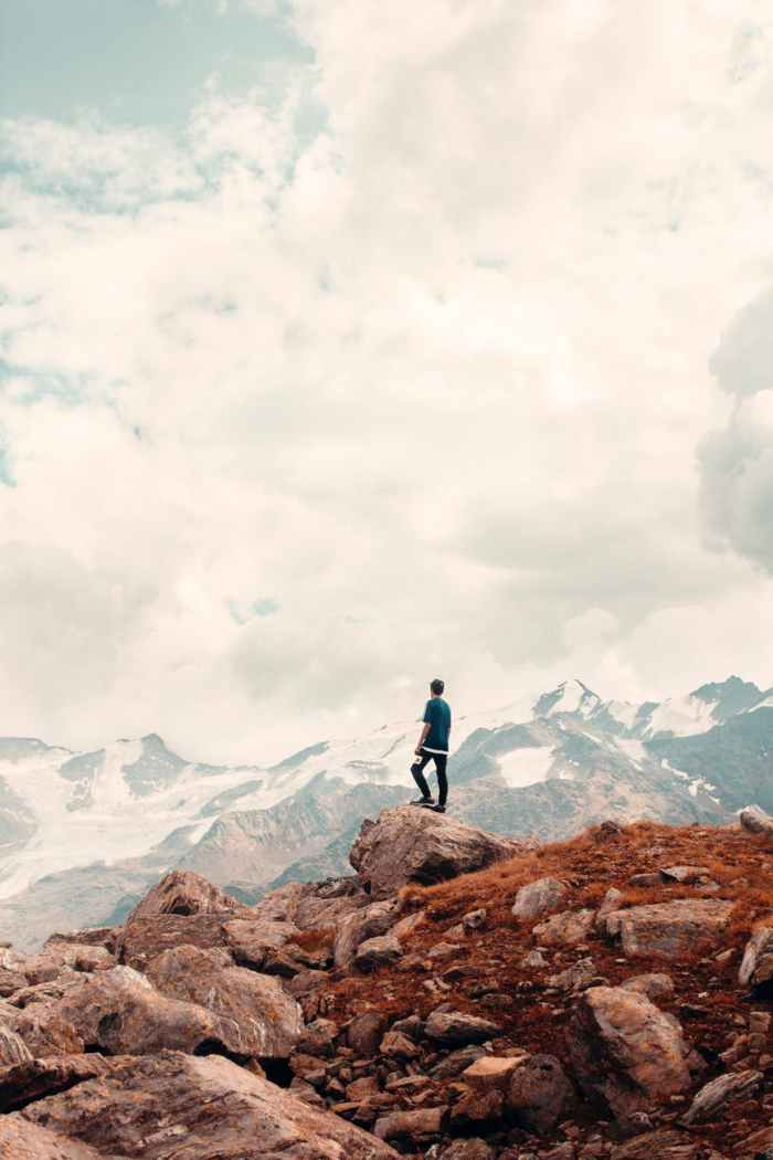 a man standing on rocky mountain under cloudy sky