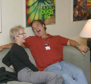 Photo of Tracy Newman and Jim Belushi seated on a couch sharing a laugh.