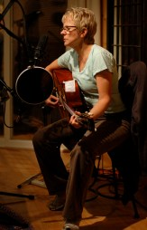 Photo of Tracy Newman seated with guitar singing into studio microphone while recording tracks in Nashville, 2009.
