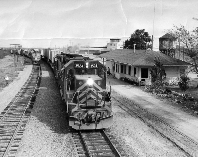 A Western Pacific freight train heads west past the Tracy depot. The bikes leaning against the depot wall belong to station agent Godwin's kids.