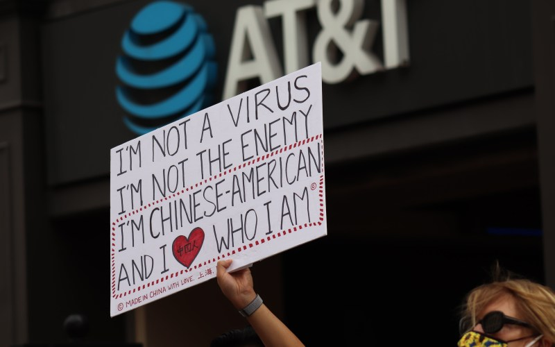 """A woman holds a sign saying """"I'm not a virus. I'm not the enemy. I'm Chinese-American, and I heart who I am."""""""