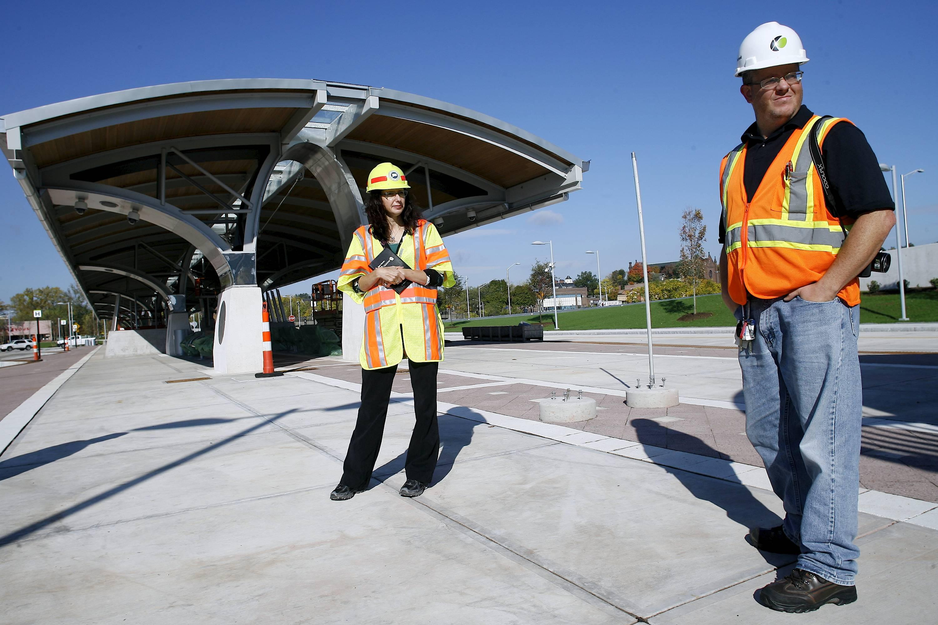 Kevin Bartram | Staff Connecticut DOT representative Lisa Rivers, left, and Tyler Tompkins from Baker Construction inspect the nearly complete downtown New Britain CTFastrak station on Friday. The dedicated busway from New Britain to Hartford is scheduled to begin service next year.