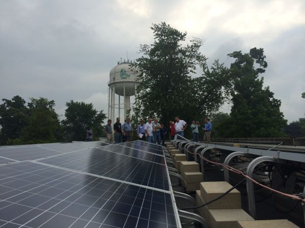 Local contractors and others peer over a solar panel array on the roof of the Porter County Career and Technical Center in August. The group participated in a Solar Ready II tour hosted by the Northwestern Indiana Regional Planning Commission.