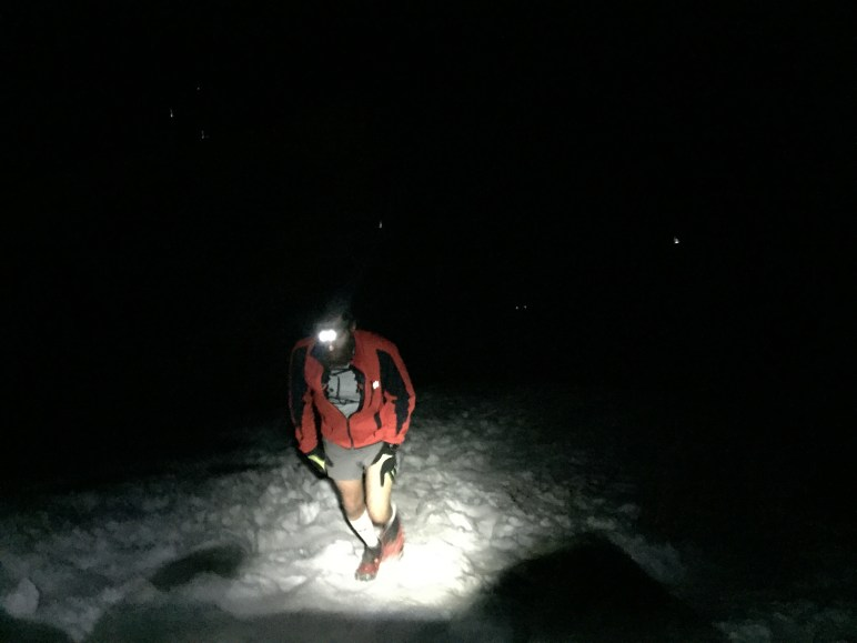 Runner reaches the summit late at night. Headlamps shine below.