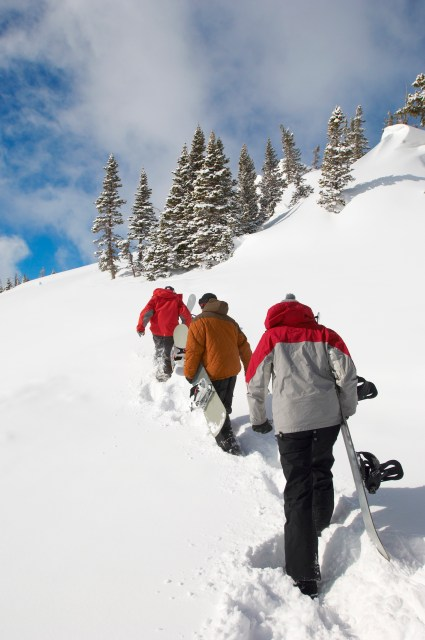 Backcountry Snowboarders Hiking up a Slope