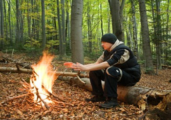 student at survival school warming hand