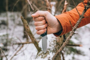 ungloved hand and knife during cold weather wilderness survival course