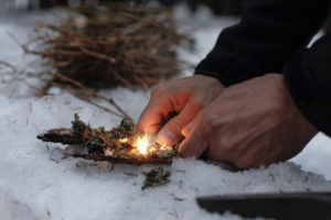 student trying to start a fire during survival classes