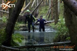To løbere forcerer en å ved Nordisk Extrem Marathon