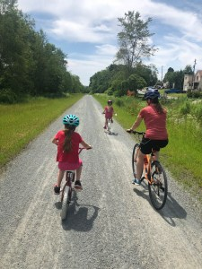 A mother and two daughters riding bikes on a trail