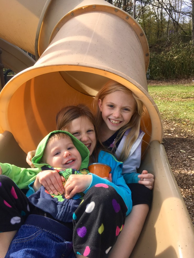 Three children at the bottom of a slide