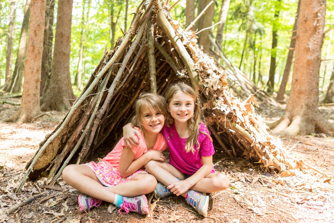 Girls outdoors under tent made of sticks