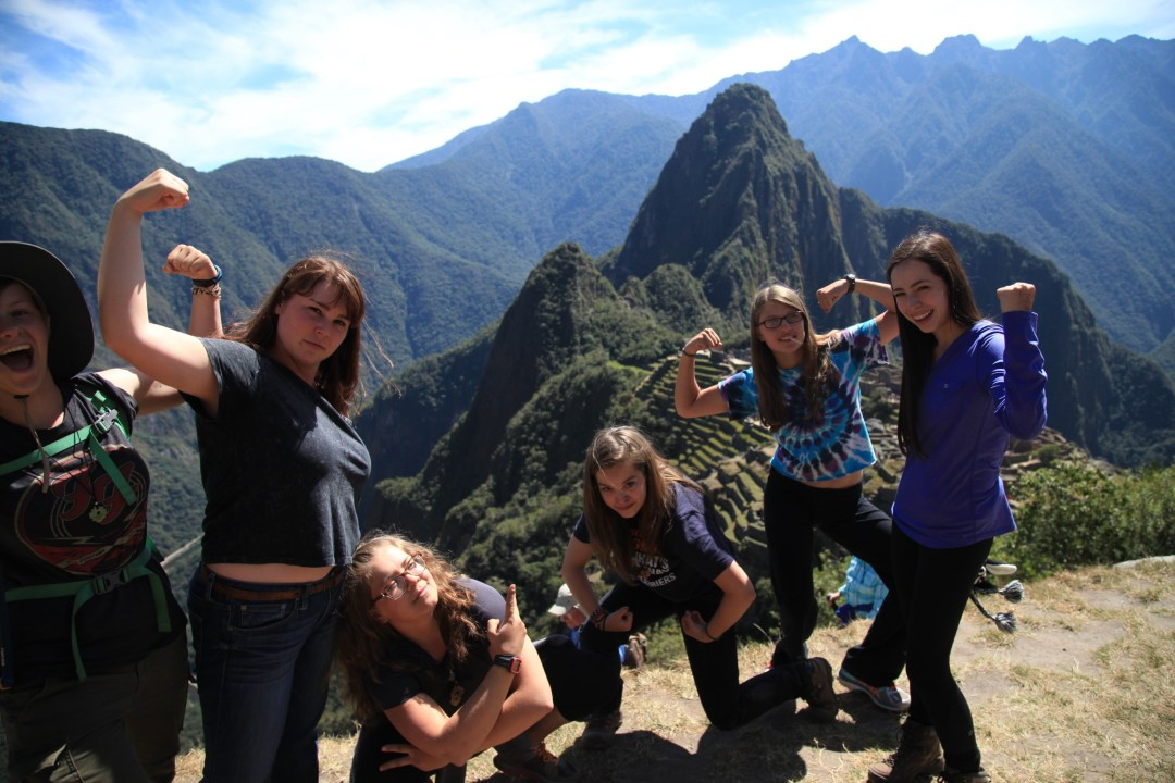 Girls show off their muscles at the top of a Peruvian mountain