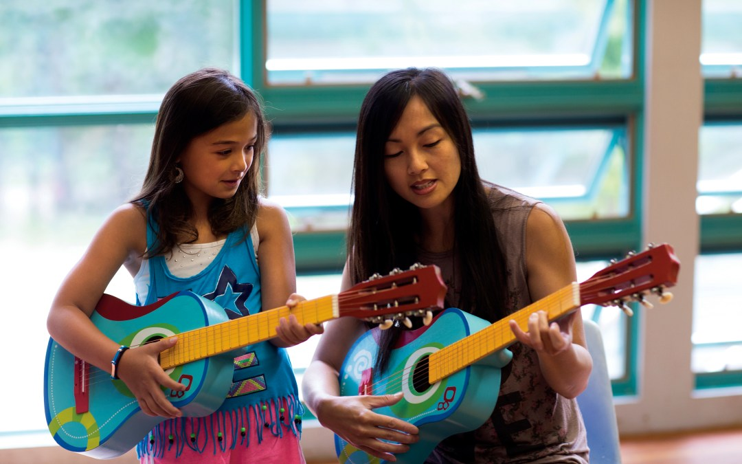 Volunteer teaching girl how to play a guitar