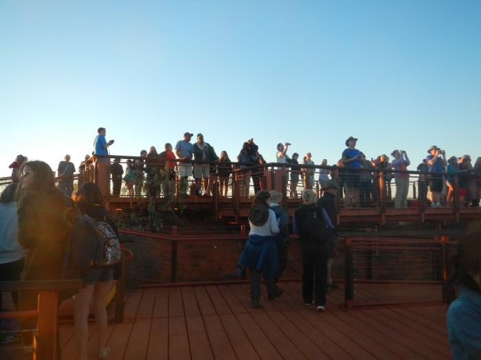A crowd in from of Uluru before sunrise