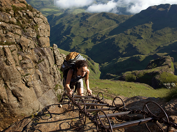 hiker climbing a chain ladder leading to the top of the amphitheatre, Drakensberg Mountain, South Africa