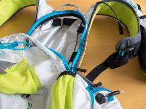 イヤフォンの延長コードが腰のポケットから肩口まで通っている。バッテリーを分離できる仕様のヘッドライトにも使えそう。
