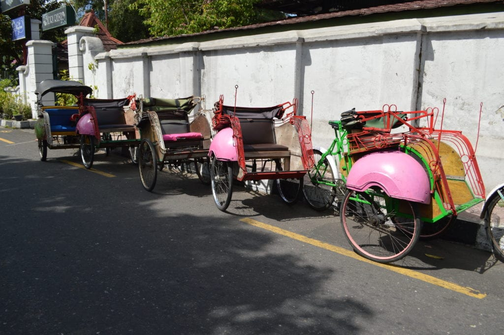Bicycle taxis line up along a whitewashed wall in the Kraton