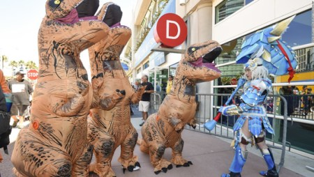Katherine Masiewicz, dressed as monster hunter, faces off against a group of dinosaurs as they pose for photographers outside the convention center on Friday, July 22, at Comic-Con San Diego. Photo courtesy CNN.