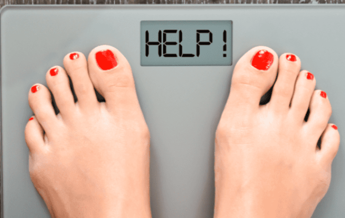Weighing on a scale to try and beat weight loss plateau