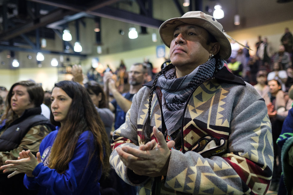 Doug Good Feather, a U.S. Army veteran, claps as Ivan Looking Horse gives a speech during a forgiveness ceremony for veterans at the Four Prairie Knights Casino & Resort on the Standing Rock Sioux Reservation on Monday, Dec. 5, 2016.