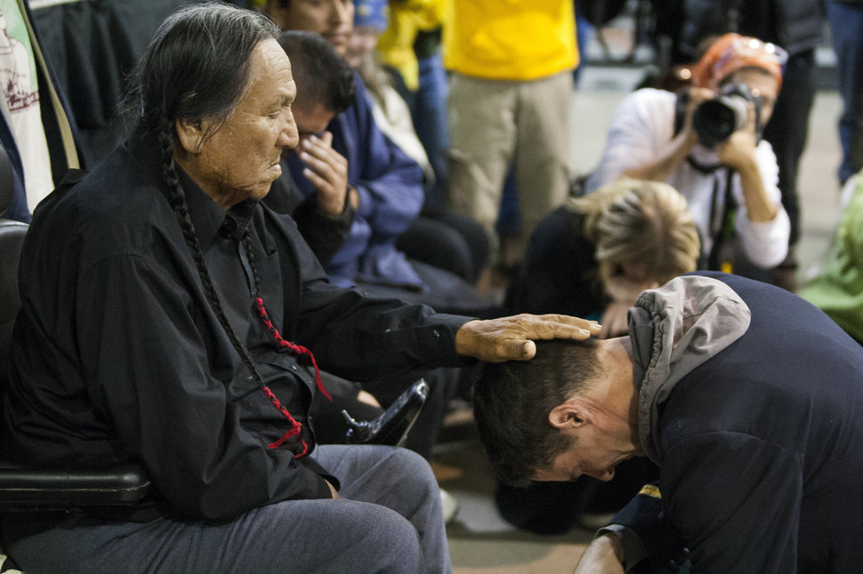 Leonard Crow Dog, a Lakota elder and highly-regarded activist, left, places his hand over Gen. Wesley Clark Jr.'s head during a forgiveness ceremony for veterans at the Four Prairie Knights Casino & Resort on the Standing Rock Sioux Reservation on Monday, Dec. 5, 2016.