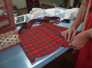 Making a cushion from an old kilt- having cut up the kilt, the pleating is put back in to keep features of the original history.