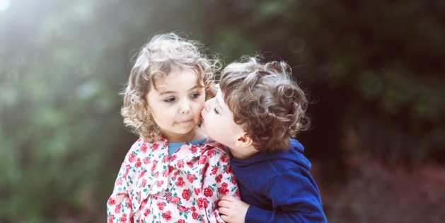 Boy kissing little girl