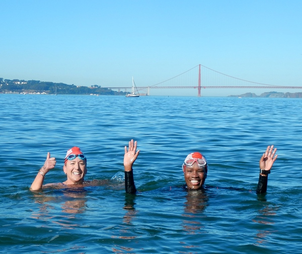 Swimmers waving to the camera in front of the Golden Gate Bridge during Take the Rock 4.0