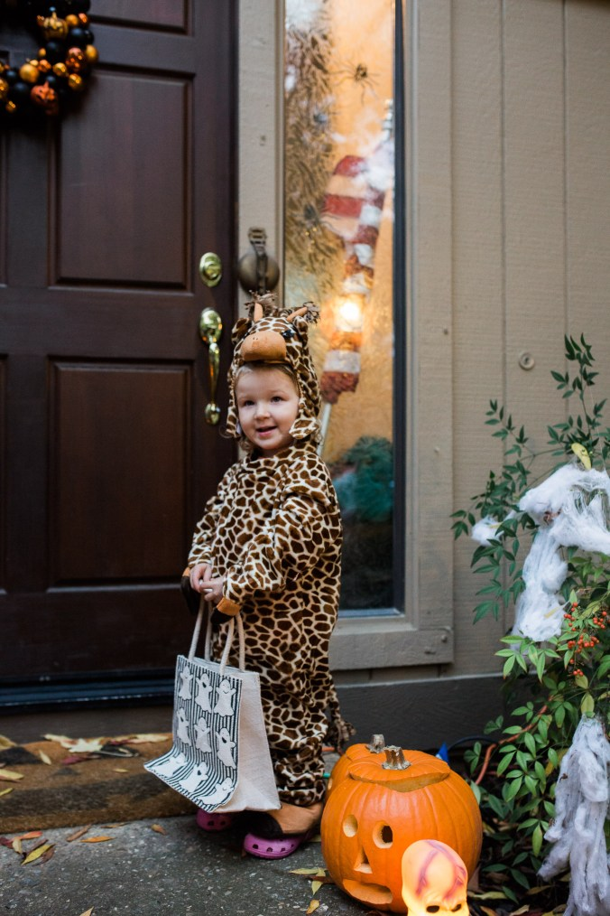 My daughter posing with her giraffe costume for Halloween