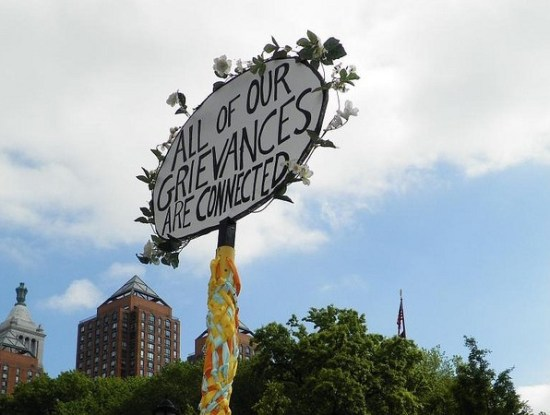 """All of our grievances are connected"" sign"