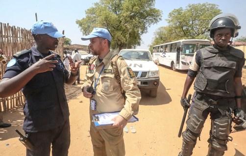 FN-politiet (UNPOL) eskorterer studentene til og fra leiren, for å sikre skolegangen. I bakgrunnen ser vi en skolebuss med elever. Kim Haugen og lokalt politi står for sikkerheten. Foto: Isaac BIlly / UNMISS.