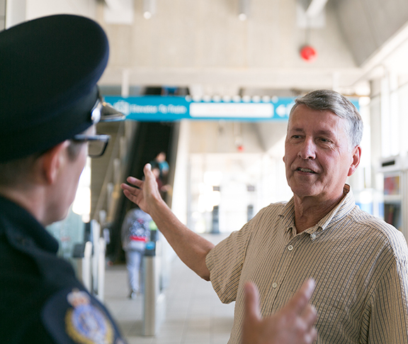 Transit Police Officer Helping a Passenger