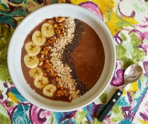 Chocolate PB smoothie bowl topped with sliced banana, chopped Reese's nut bar, oats and chia seeds.