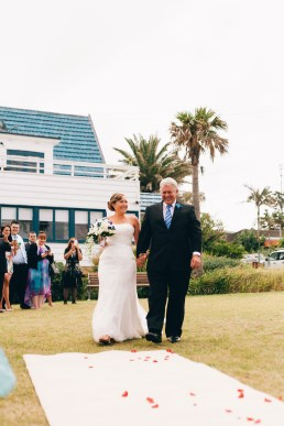father holding hands with the bride as they walk down the aisle wedding ceremony