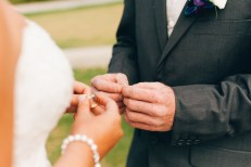 groom puts the ring on the bride's hand during ceremony