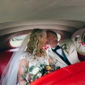 bride and groom in vintage wedding car kissing