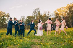 bride and groom bridal party tug of war kissing