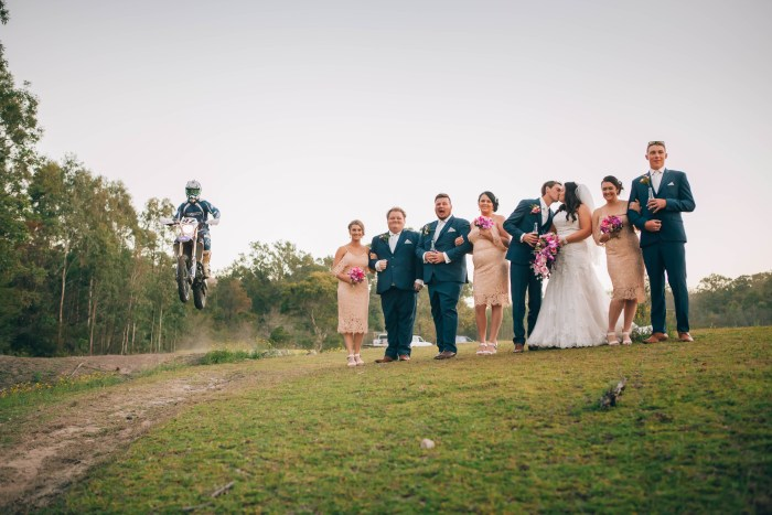 Bridal party with bride and groom kissing with dirtbike jump