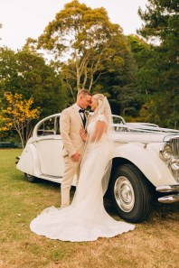 wedding couple standing next to vintage wedding car at rhodendendron gardens wollongong