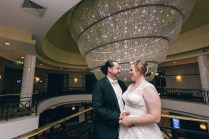 beautiful aussie bride and groom kissing under chandelier
