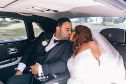 bride and groom kissing in rolls royce phantom