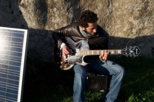 Daniele Pisasale making sounds on his solar powered electric GTR at Argimusco. The GTR amplifier is powered by a battery that is loaded by the sun and passes through an inverter that gives 220V power. The inverter has also 5V USB power out to reload your USB powered batteries.