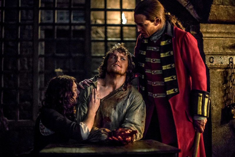 Capt. Jack Randall (Tobias Menzies) tortures Jamie Fraser (Sam Heughan) while a helpless Claire (Caitriona Balfe) looks on in the season one finale of Starz's Outlander
