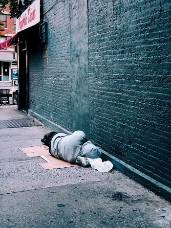 A homeless man lies alone on the street next to a bare wall.